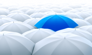 Group of White Umbrellas with One in Bright Blue to Stand Out from the Crowd